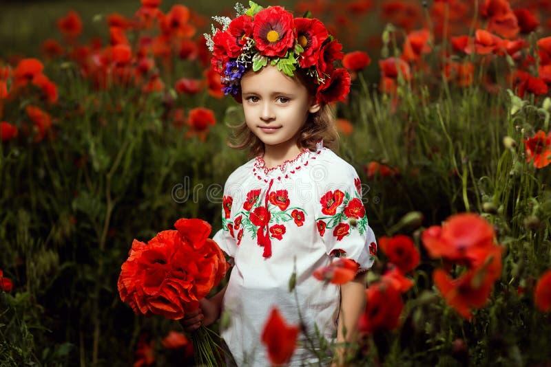 Kleines Mädchen auf dem Mohnblumegebiet stockbilder