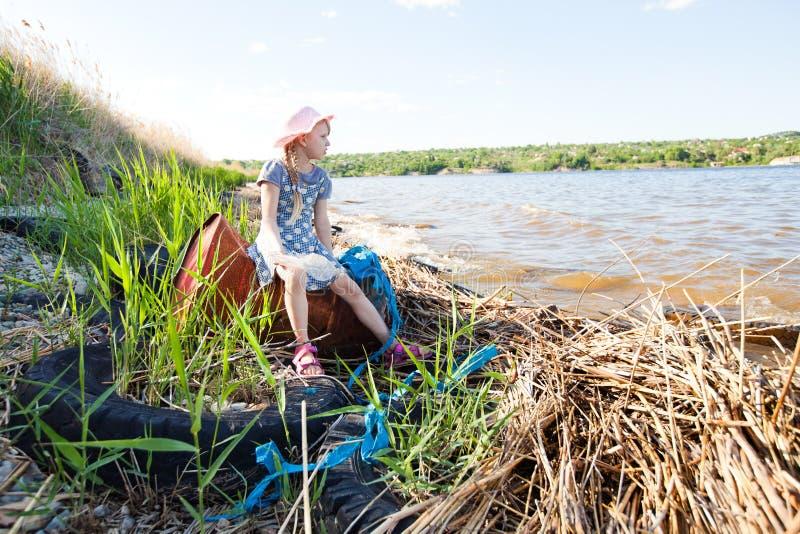 Kleines Mädchen auf der Bank von Fluss mit Abfall stockbild