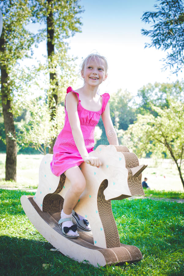 Kleines Mädchen auf einem Spielzeugeinhorn Grasartiges Feld am Park Baum auf dem Gebiet Mädchenlächeln und she& x27; s glücklich stockfotografie