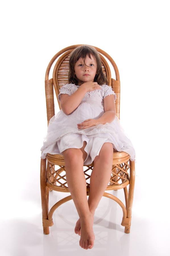Kleines Mädchen auf einem Stuhl stockbilder