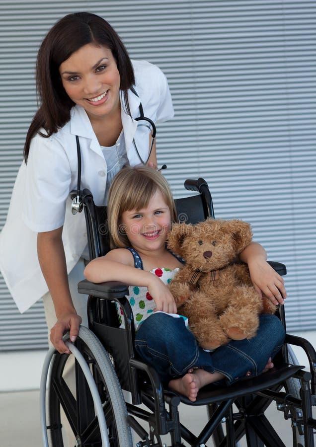 Kleines Mädchen auf einer Rollstuhlholding ihr Teddybär stockfotos