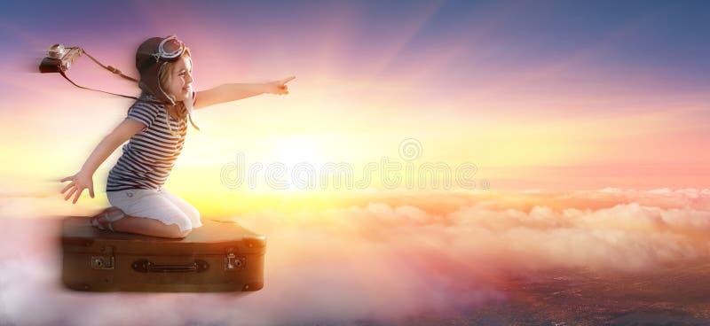 Kleines Mädchen auf Koffer in der Reise über Wolken stockbilder