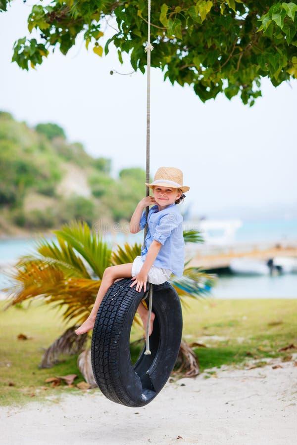 Kleines Mädchen auf Reifenschwingen stockfotos