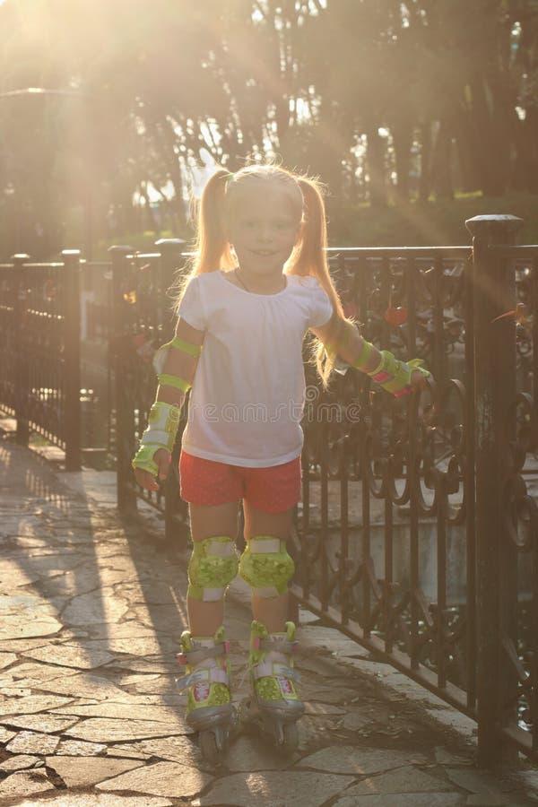 Kleines Mädchen auf Rollschuhen wirft nahe Geländer in sonniger SU auf stockbilder