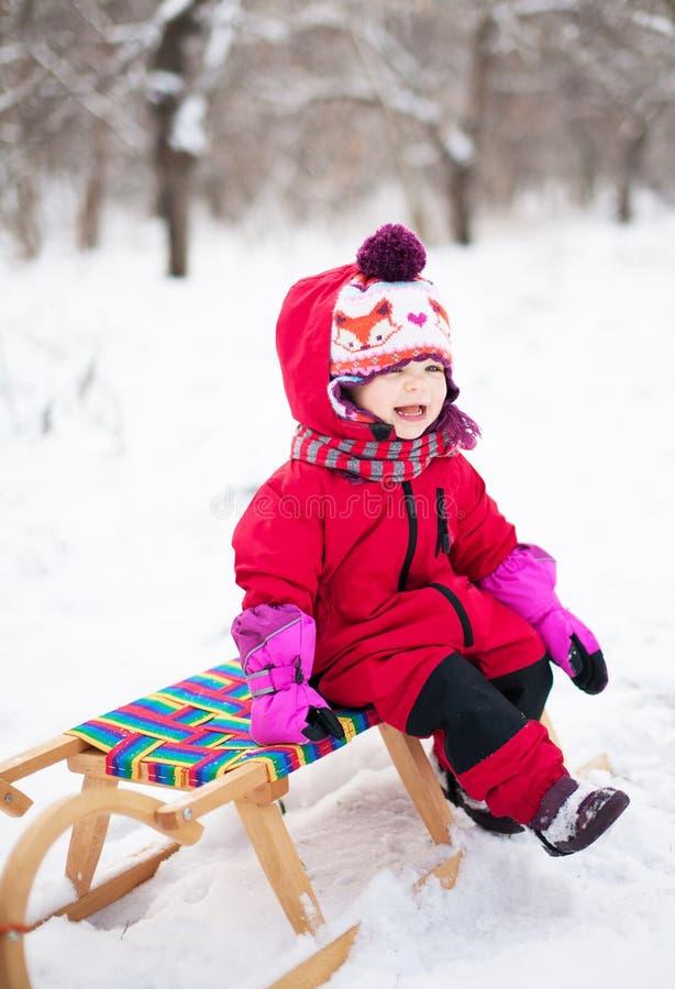 Kleines Mädchen auf Schlitten stockfoto