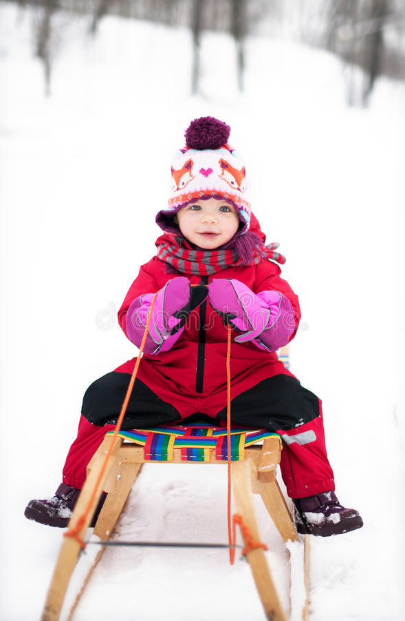 Kleines Mädchen auf Schlitten lizenzfreies stockfoto