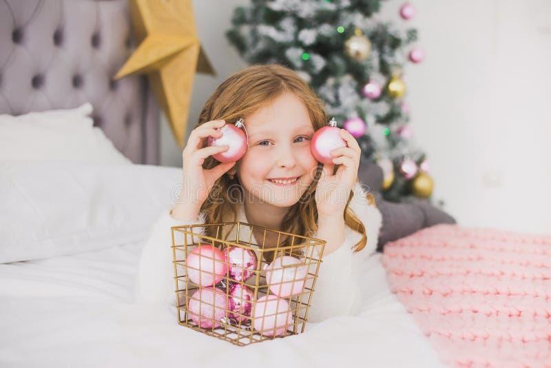 Kleines Mädchen auf Weihnachtsmorgen im Hauptinnenraum lizenzfreie stockbilder