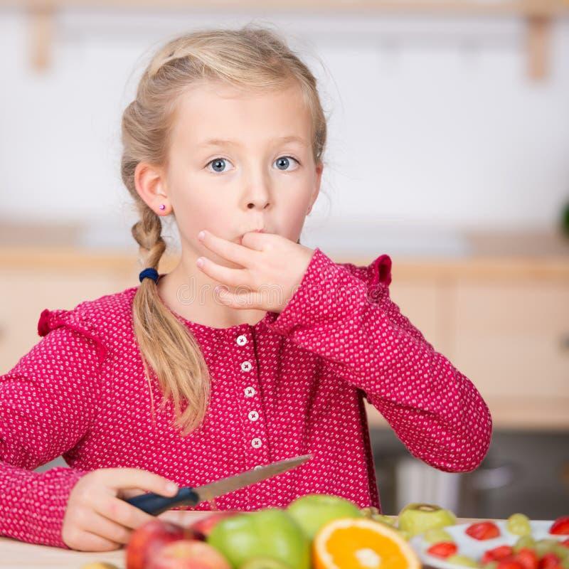 Kleines Mädchen-Ausschnitt-Frucht in der Küche stockbilder