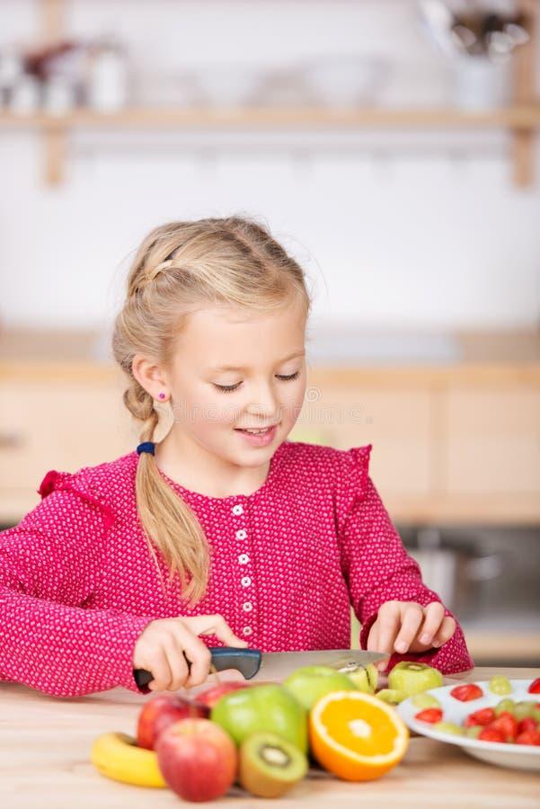 Kleines Mädchen-Ausschnitt-Frucht in der Küche stockfotos
