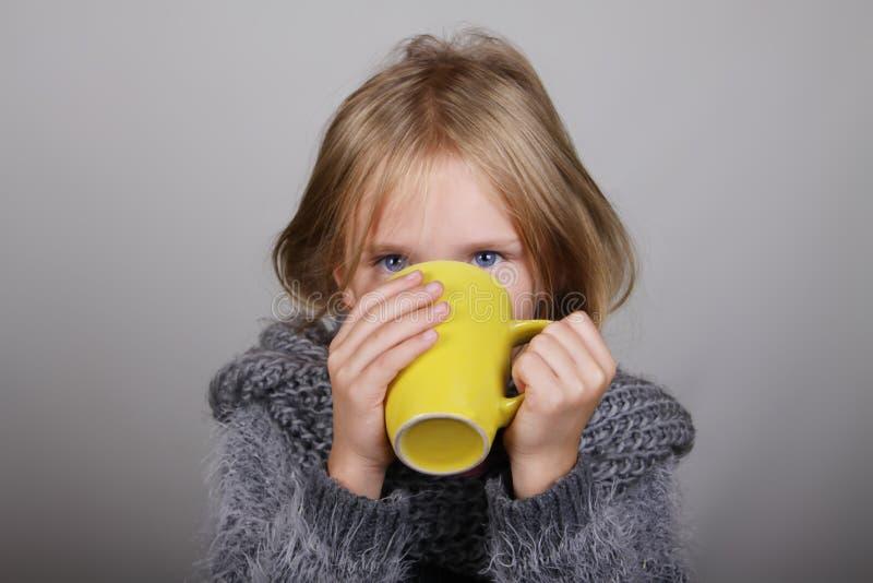 Kleines Mädchen Bblond-Haares ein Schale heißen Tee in den Händen Krankes Kind Kinderwintergrippe-Gesundheitswesenkonzept lizenzfreie stockbilder