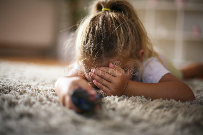 Kleines Mädchen bedeckte Augen beim Fernsehen lizenzfreie stockfotografie