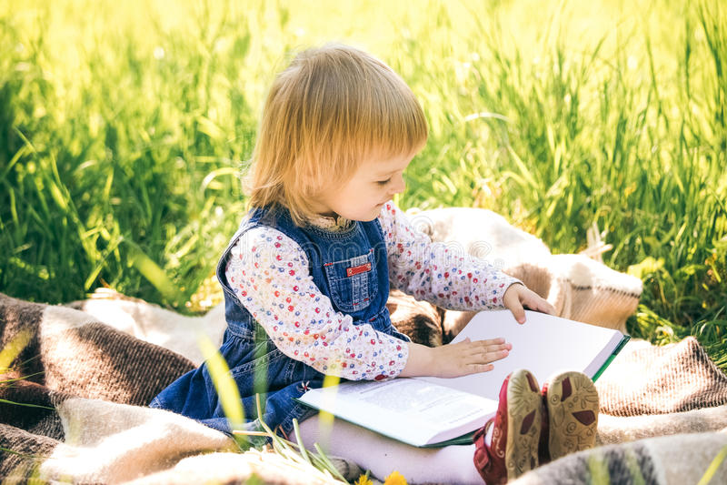 Kleines Mädchen betrachtet Seiten des Buches stockbild
