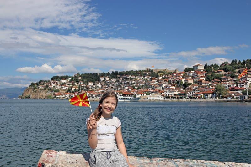 Kleines Mädchen bewegt mit einer mazedonischen Flagge auf See Ohrid wellenartig stockfotografie
