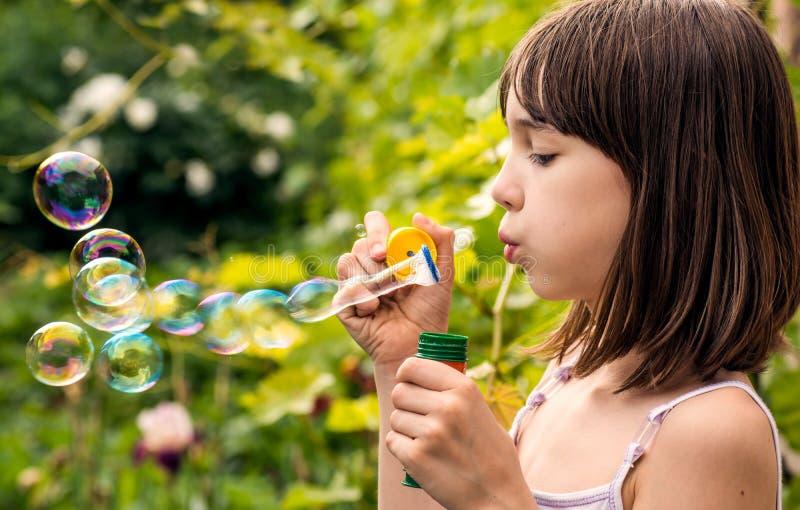Kleines Mädchen bläst Seifenblasen im Garten auf, stockbilder