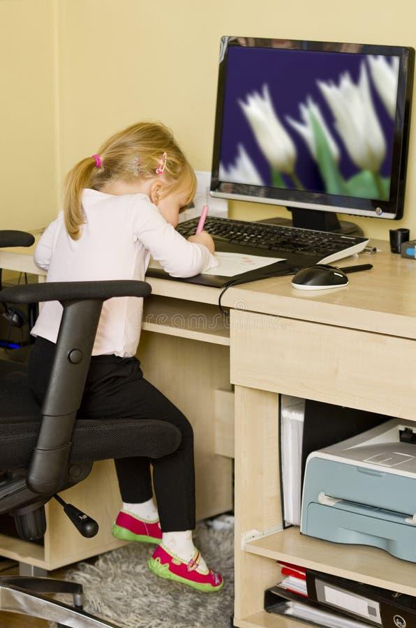 Kleines Mädchen am Computerschreibtisch lizenzfreie stockfotografie