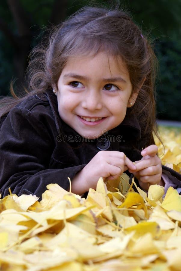 Kleines Mädchen, das über Herbstblättern niederlegt stockfotos