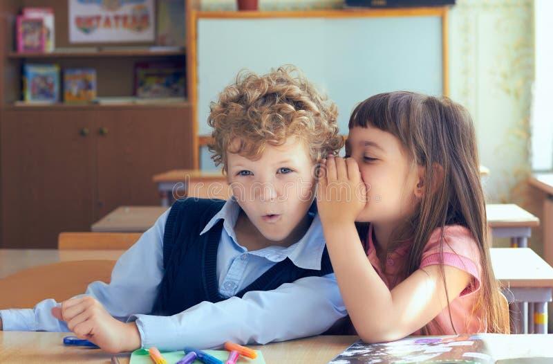 Kleines Mädchen, das überraschtem Jungen im Klassenzimmer Geheimnis sagt stockbild