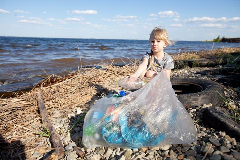 Kleines Mädchen, das Abfall sammelt stockbild
