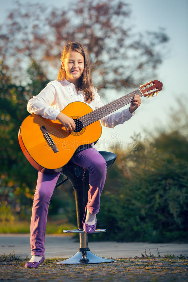 Kleines Mädchen, das Akustikgitarre spielt stockfotografie