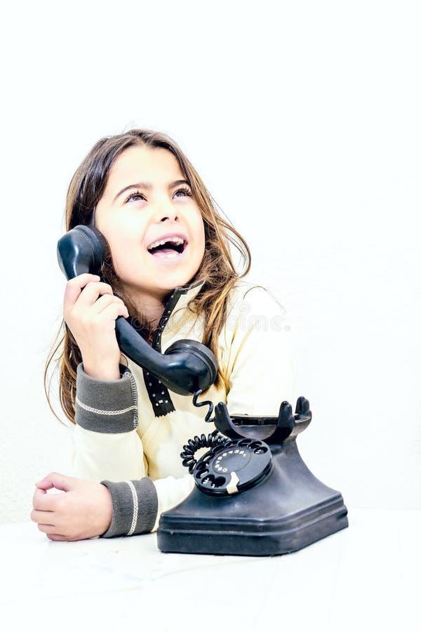 Kleines Mädchen, das am alten Weinlesetelefon spricht lizenzfreie stockbilder