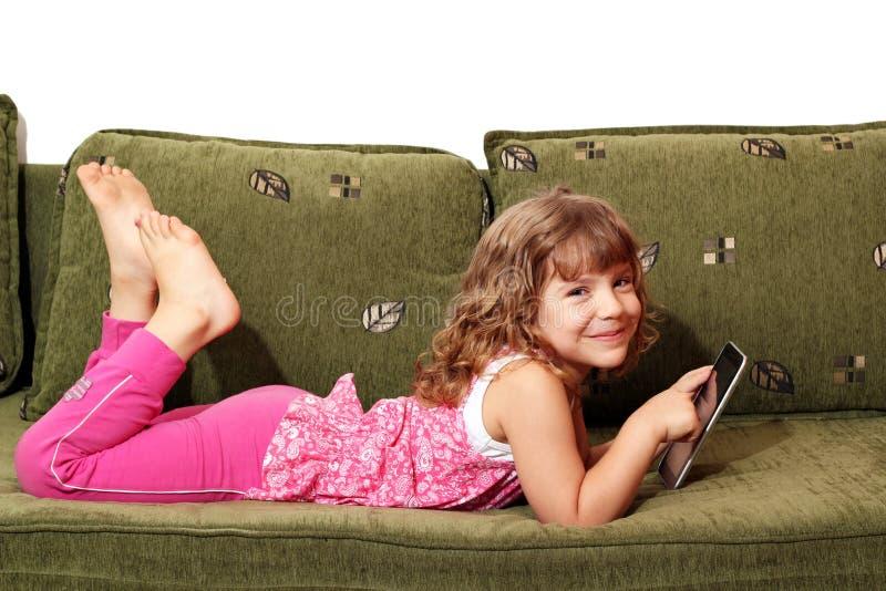 Kleines Mädchen, das auf Bett mit Tablette liegt lizenzfreie stockfotografie