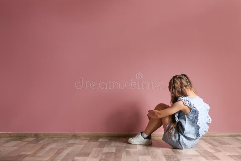 Kleines Mädchen, das auf Boden nahe Farbwand im leeren Raum sitzt lizenzfreie stockbilder