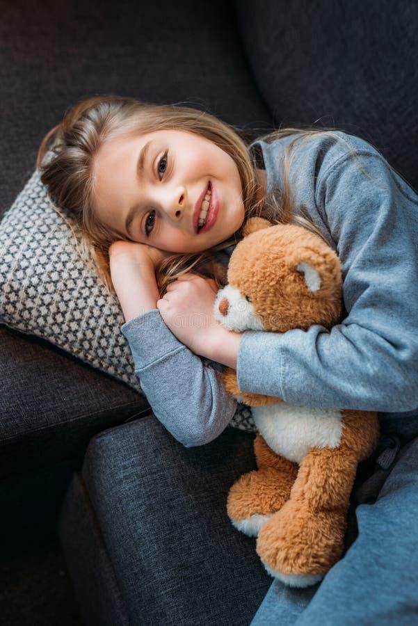 Kleines Mädchen, das auf Couch mit Teddybären liegt und an der Kamera lächelt lizenzfreie stockbilder