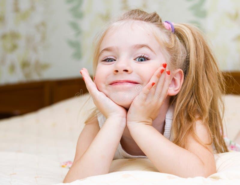 Kleines Mädchen, das auf dem Bett liegt lizenzfreie stockfotos