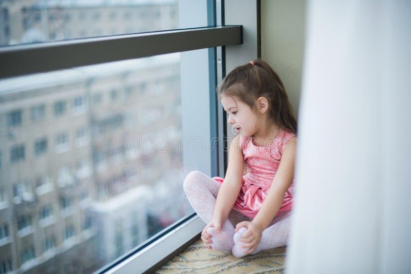 Kleines Mädchen, das auf dem Boden und dem Lächeln sitzt lizenzfreie stockfotografie