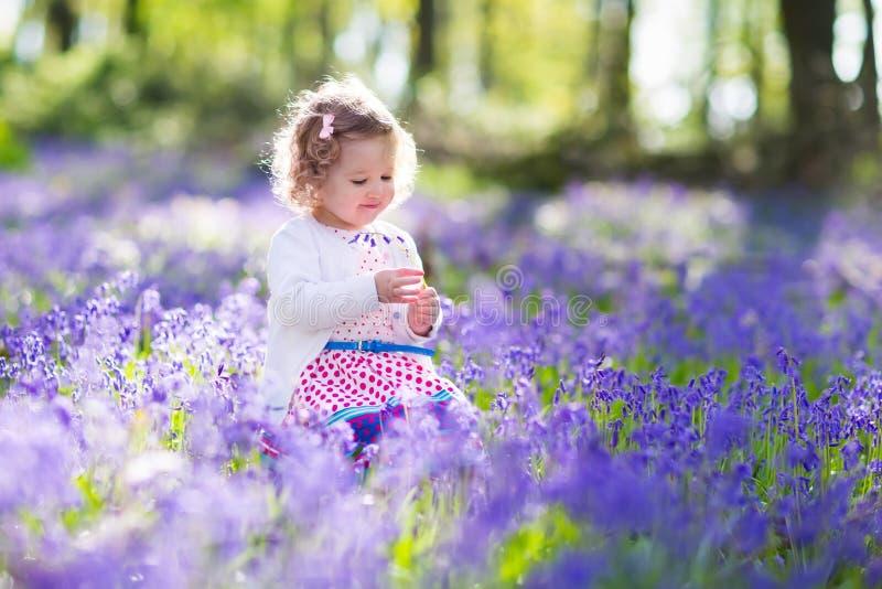 Kleines Mädchen, das auf dem Glockenblumeblumengebiet spielt stockfotografie