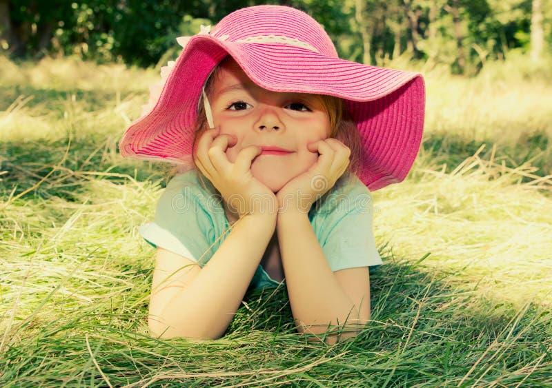 Kleines Mädchen, das auf dem Gras im Freien liegt Lächelnde Mädchengesichtsnahaufnahme lizenzfreie stockbilder
