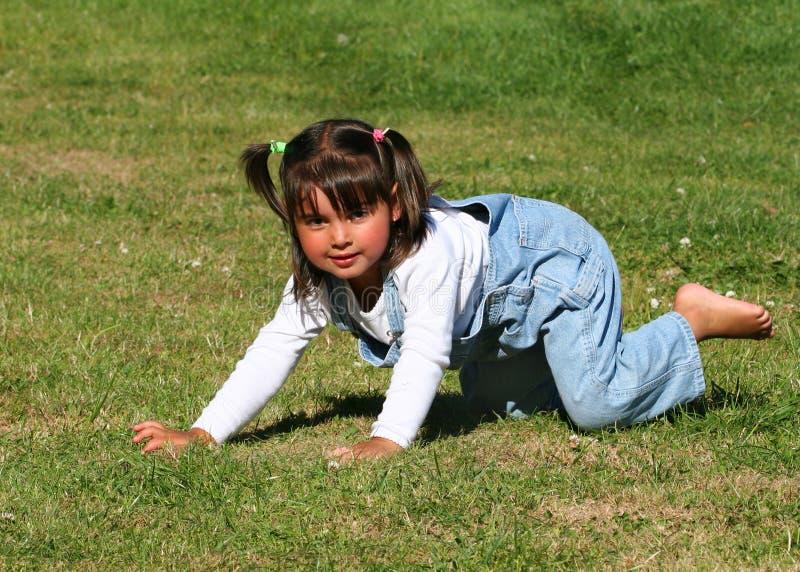 Kleines Mädchen, das auf dem Gras spielt lizenzfreies stockfoto
