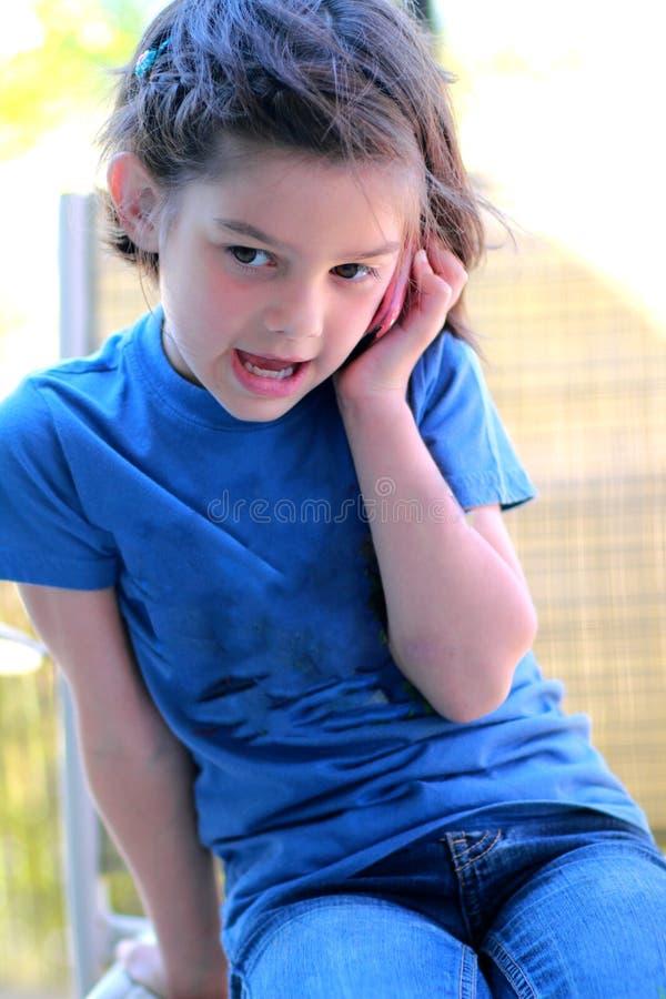 Kleines Mädchen, das auf dem Handy spricht stockfoto