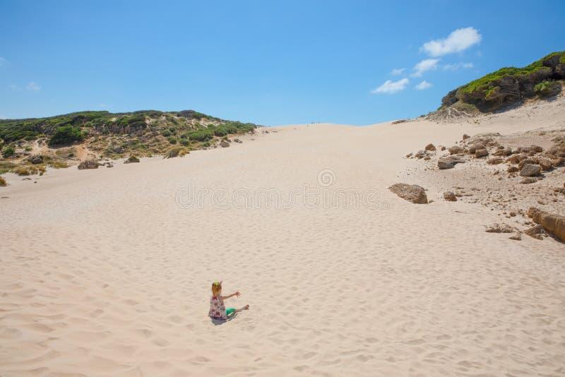 Kleines Mädchen, das auf dem Sand nennt Spitze der Düne im Horizont sitzt stockbild