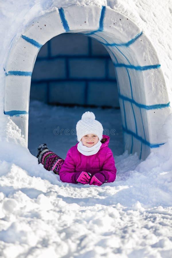 Kleines Mädchen, das auf dem Schnee nahe dem Eingang zum Iglu liegt stockbilder