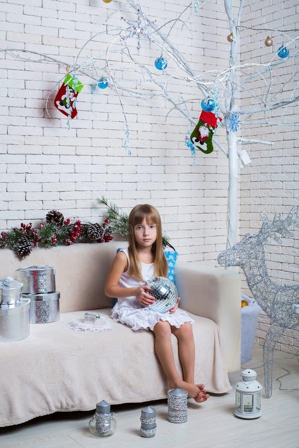 Kleines Mädchen, das auf dem Sofa mit Weihnachtsgeschenken sitzt stockbilder