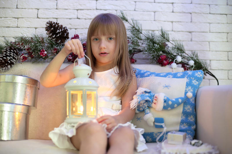 Kleines Mädchen, das auf dem Sofa mit Weihnachtsgeschenken sitzt lizenzfreies stockbild