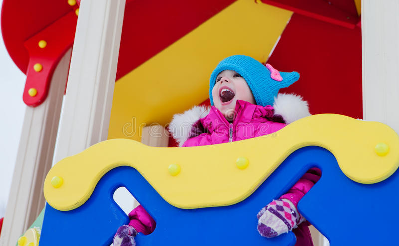 Kleines Mädchen, das auf dem Spielplatz, den Spaß habend spielt, der den Tag des Winters auf der Straße spinnend im Park spielt stockbild