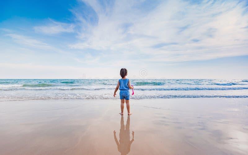 Kleines Mädchen, das auf dem Strand im Sonnenuntergang spielt stockfotos