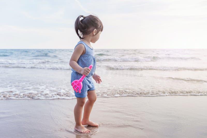 Kleines Mädchen, das auf dem Strand im Sonnenuntergang spielt lizenzfreie stockbilder