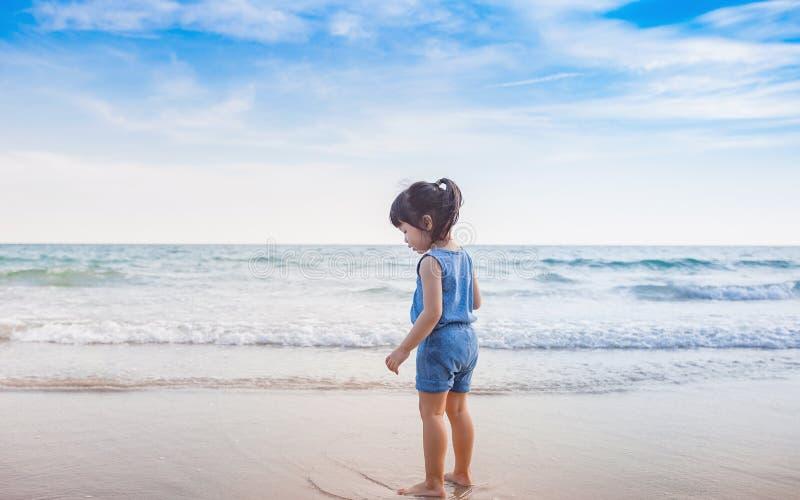 Kleines Mädchen, das auf dem Strand im Sonnenuntergang spielt stockbild