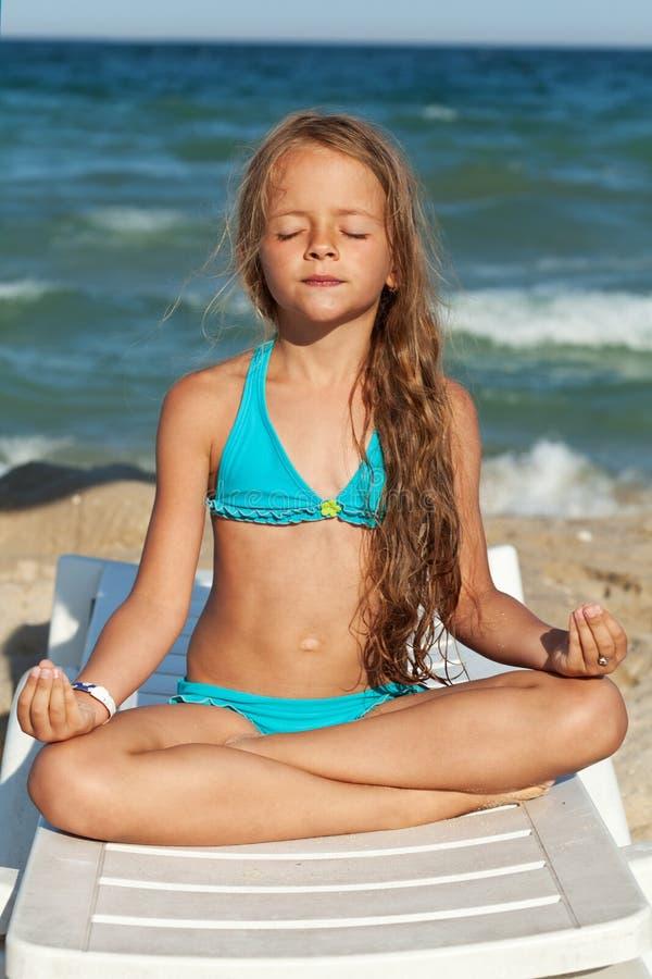 Kleines Mädchen, das auf dem Strand sich entspannt lizenzfreies stockbild