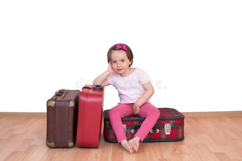 Kleines Mädchen, das auf dem Weinlesekoffer lokalisiert sitzt stockbilder