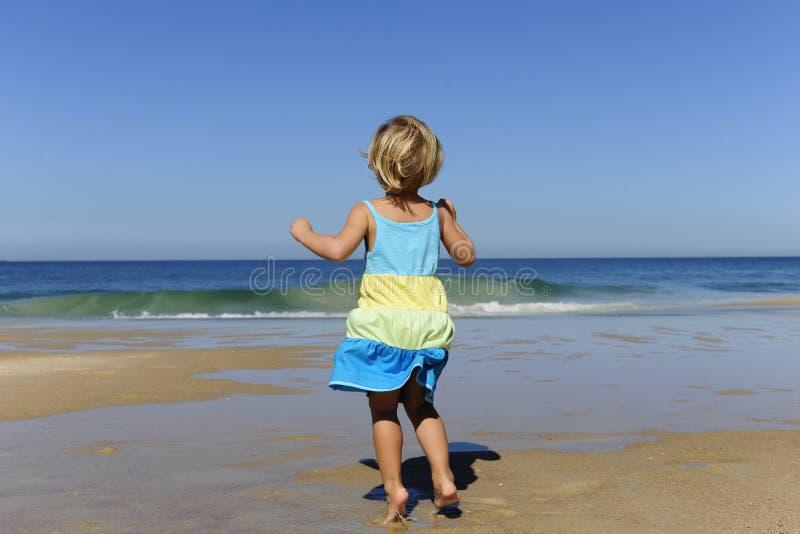 Kleines Mädchen, das auf den Strand springt stockfotografie
