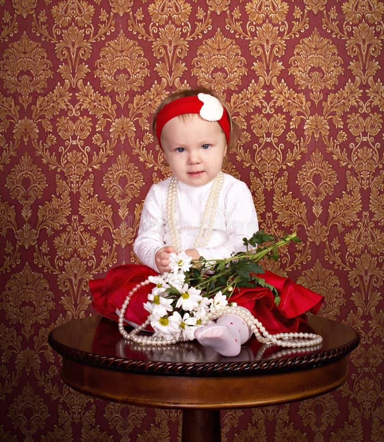Kleines Mädchen, das auf der Tabelle sitzt lizenzfreie stockfotos