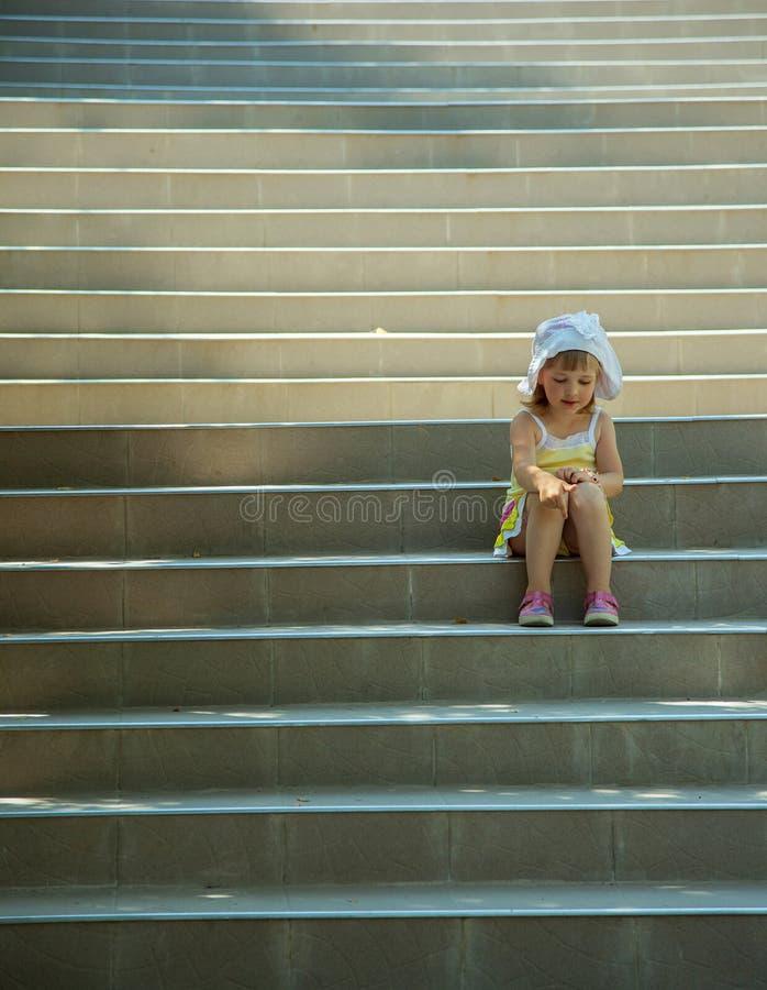 Kleines Mädchen, das auf der Treppe sitzt lizenzfreie stockfotos