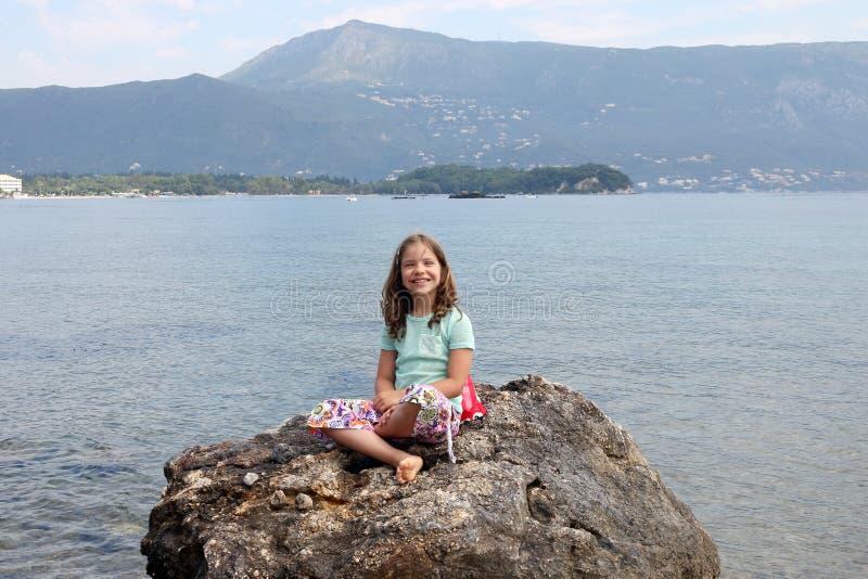 Kleines Mädchen, das auf einem Felsen durch das Meer sitzt lizenzfreies stockfoto