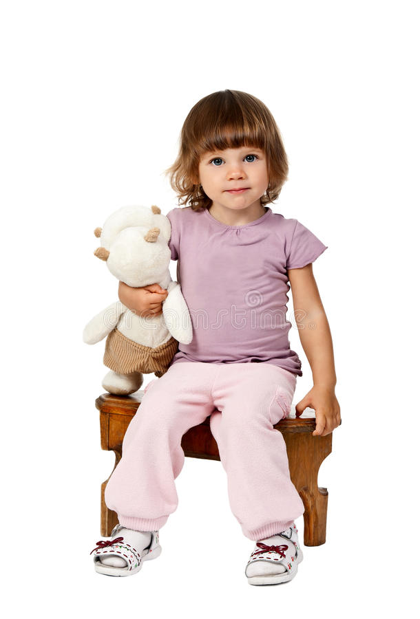 Kleines Mädchen, das auf einem hölzernen Schemel sitzt stockfotografie