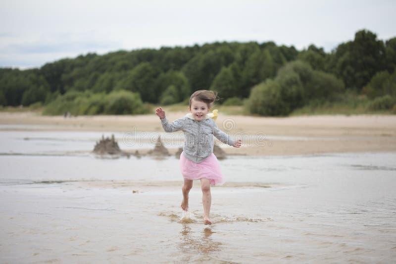 Kleines Mädchen, das auf einem sandigen Seeufer läuft lizenzfreies stockbild