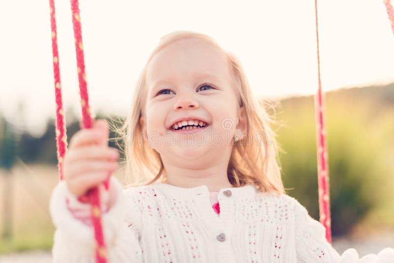Kleines Mädchen, das auf einem Spielplatz schwingt Kindheit, glücklich, Sommer-Konzept im Freien lizenzfreie stockfotografie